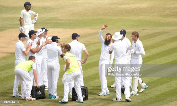 Moeen Ali of England is applauded by teammates and the crowd as he shows off the ball after taking his fifth wicket of India's 2nd innings of the 3rd...