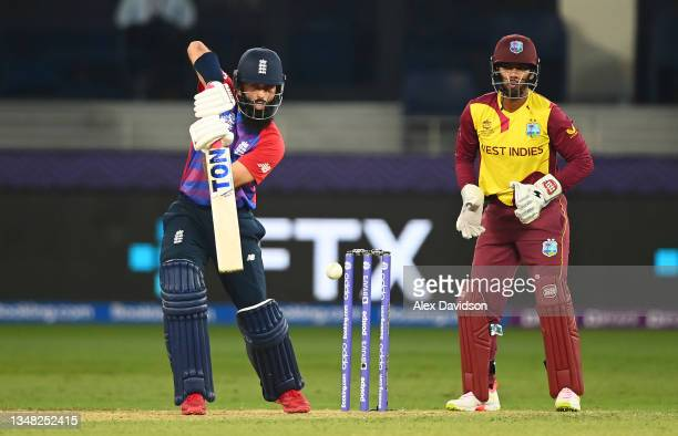 Moeen Ali of England plays a shot as Nicholas Pooran of West Indies looks on during the ICC Men's T20 World Cup match between England and Windies at...