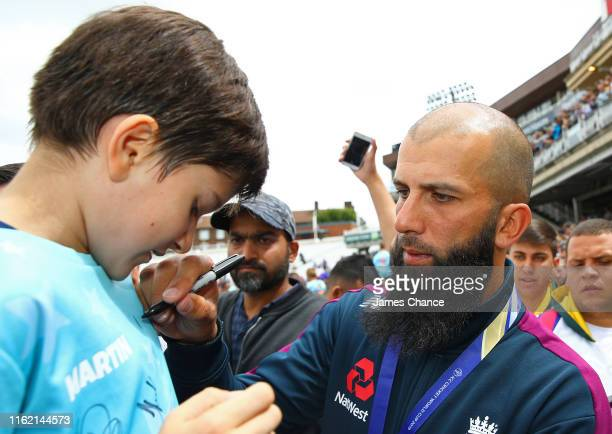 Moeen Ali of England signs a autograph during the England ICC World Cup Victory Celebration at The Kia Oval on July 15 2019 in London England