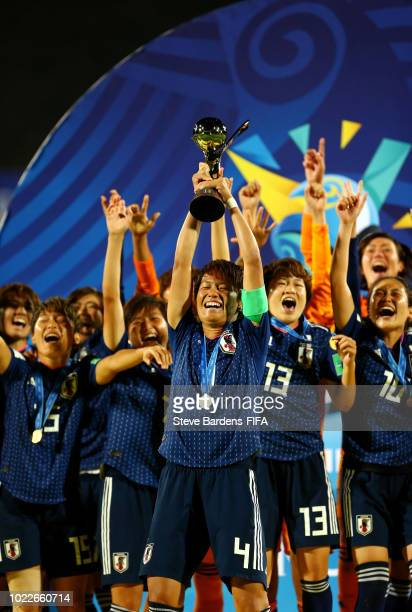 Moeka Minami of Japan lifts the trophy as Japan celebrate victory following the FIFA U-20 Women's World Cup France 2018 Final match between Spain and...