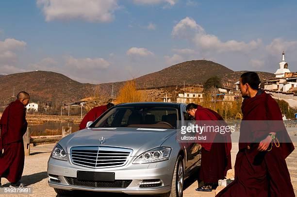 Moenche betrachten einen Mercedes Benz vor dem Kloster Gandem Sumtseling