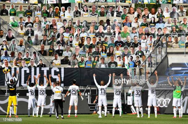 Moenchengladbach players celebrate in front of the cardboard cut outs with photos of Moenchengladbach fans displayed on the stands during the...