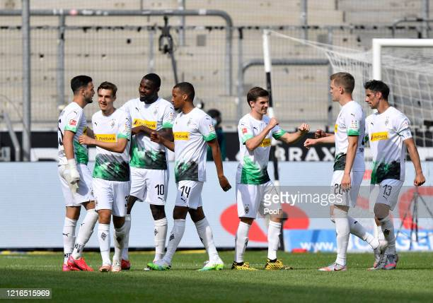 Moenchengladbach's Alassane Plea celebrates with teammates after scoring his side's fourth goal during the Bundesliga match between Borussia...