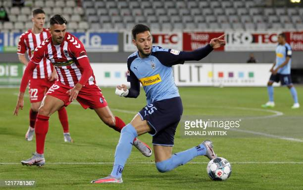 Moenchengladbach's Algerian defender Ramy Bensebaini and Freiburg's Italian midfielder Vincenzo Grifo vie for the ball during the German first...