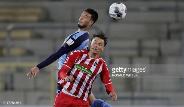 Moenchengladbach's Algerian defender Ramy Bensebaini and Freiburg's German defender Robin Koch both jump to head the ball during the German first...