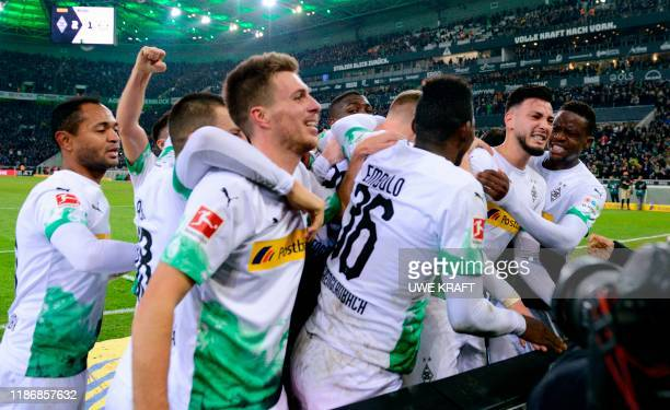 Moenchengladbach's Algerian defender Ramy Bensebaini celebrates with teammates after scoring at the end of the German first division Bundesliga...