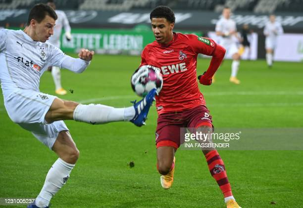 Moenchengladbach's Austrian defender Stefan Lainer and Cologne's German defender Ismail Jakobs vie for the ball during the German first division...