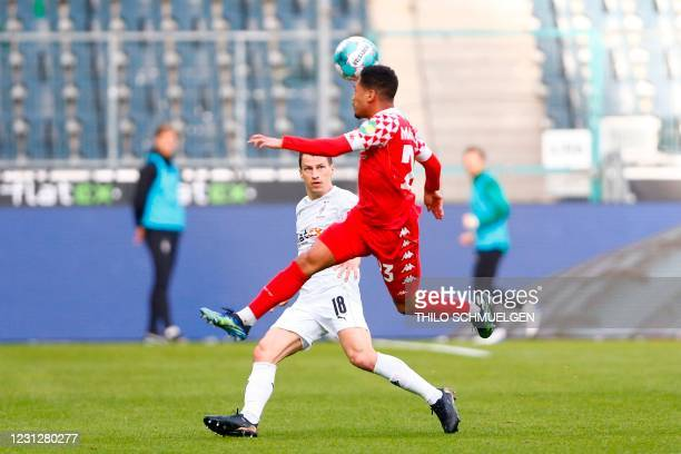 Moenchengladbach's Austrian defender Stefan Lainer and Mainz' Austrian defender Philipp Mwene fight for the ball during the German first division...