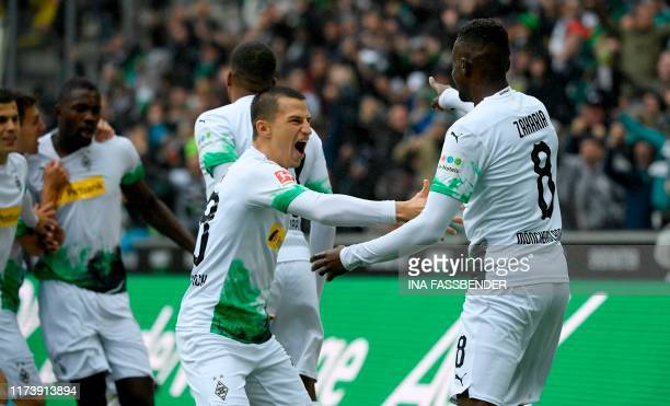 Moenchengladbach's Austrian defender Stefan Lainer congratulates Moenchengladbach's Swiss midfielder Denis Zakaria after he scored the 10 goal during...