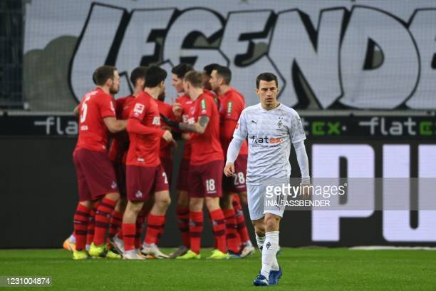 Moenchengladbach's Austrian defender Stefan Lainer reacts as Cologne's players celebrates scoring the opening goal during the German first division...
