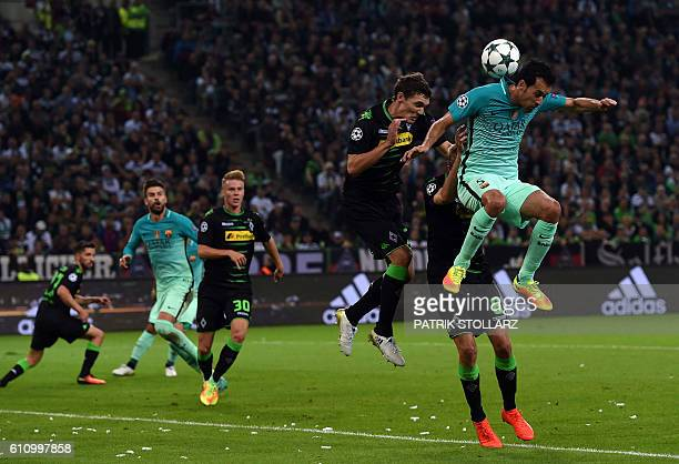 Moenchengladbach's Danish defender Andreas Christensen and Barcelona's midfielder Sergio Busquets vie for the ball during the UEFA Champions League...