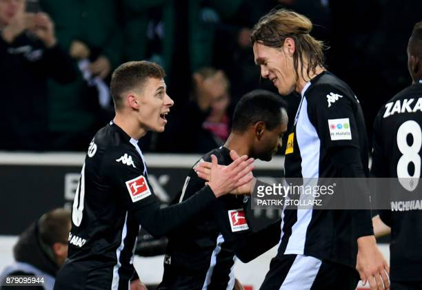 Moenchengladbach's Danish defender Jannik Vestergaard congratulates his teammate Belgian midfielder Thorgan Hazard after he scored a goal during the...