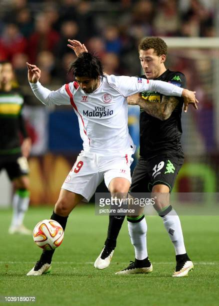 Moenchengladbach's Fabian Johnson and Sevilla's Ever Banega vie for the ball during the Europa League Round of 32 soccer match between Sevilla FC and...