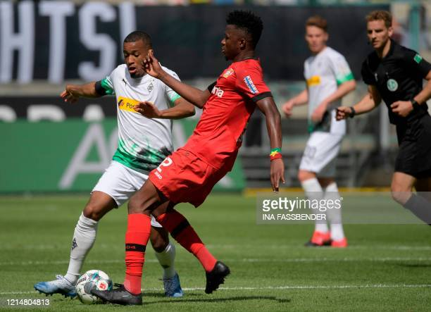 Moenchengladbach's French forward Alassane Plea and Leverkusen's Burkinabe defender Edmond Tapsoba vie for the ball during the German first division...