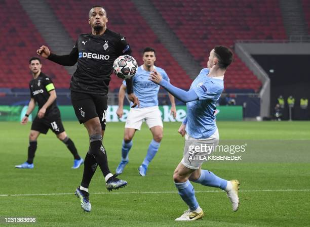 Moenchengladbach's French forward Alassane Plea and Manchester City's English midfielder Phil Foden vie for the ball during the UEFA Champions...