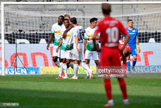 Moenchengladbach's French forward Alassane Plea celebrates with teammates after scoring the 41 during the German first division Bundesliga football...