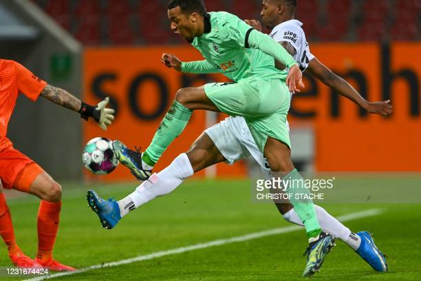 Moenchengladbach's French forward Alassane Plea has an attempt on goal blocked by Augsburg's British midfielder Reece Oxford and Augsburg's Polish...