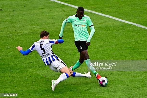 Moenchengladbach's French forward Marcus Thuram and Hertha Berlin's German defender Niklas Stark vie for the ball during the German first division...