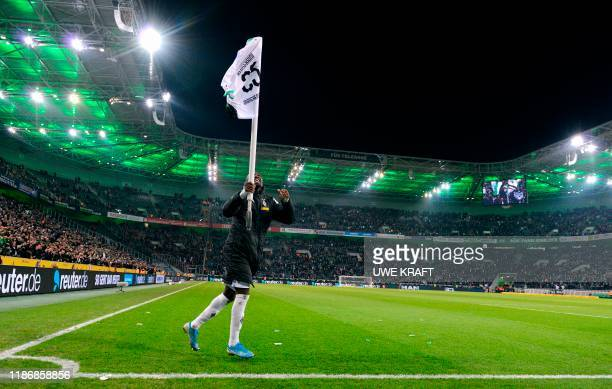 Moenchengladbach's French forward Marcus Thuram carries the corner flag with the jersey of his teammate Bensebaini as he celebrates after the German...