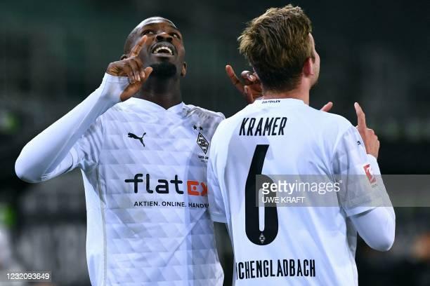 Moenchengladbach's French forward Marcus Thuram celebrates after scoring with Moenchengladbach's German midfielder Christoph Kramer during the German...