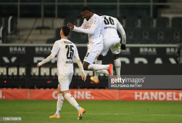 Moenchengladbach's French forward Marcus Thuram celebrates scoring his team's fourth goal with Moenchengladbach's Swiss forward Breel Embolo during...