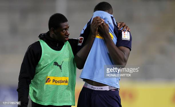 Moenchengladbach's French forward Marcus Thuram is consoled by Moenchengladbach's French defender Mamadou Doucoure after the German first division...