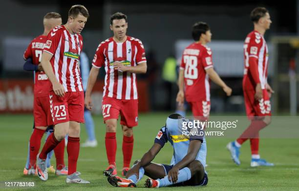 Moenchengladbach's French forward Marcus Thuram reacts on the ground after the German first division Bundesliga football match SC Freiburg v Borussia...