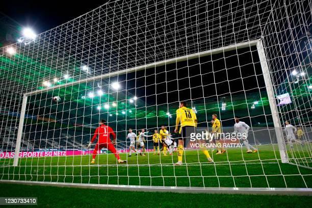 Moenchengladbach's French forward Marcus Thuram scores his team's fourth goal against Dortmund's Swiss goalkeeper Roman Buerki during the German...