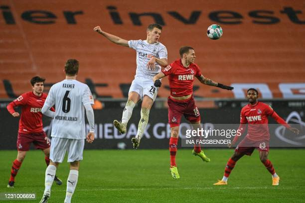 Moenchengladbach's German defender Matthias Ginter and Cologne's Slovak midfielder Ondrej Duda both jump to head the ball during the German first...