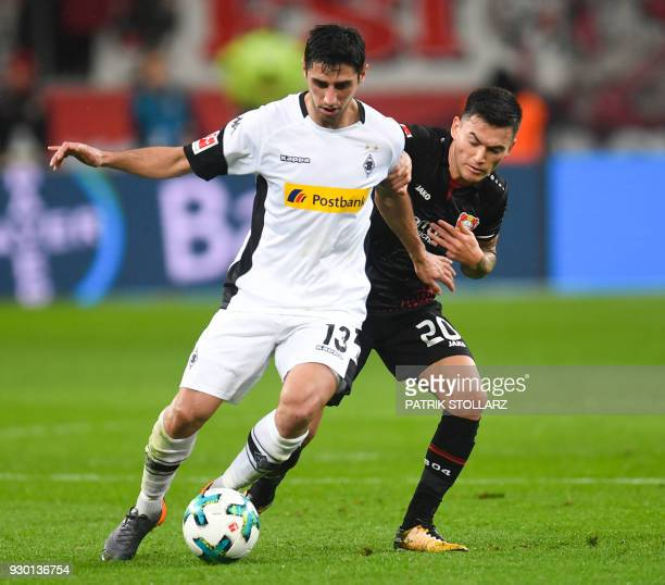 Moenchengladbach's German forward Lars Stindl and Leverkusen's Chilean midfielder Charles Mariano Aranguiz vie for the ball during the German first...