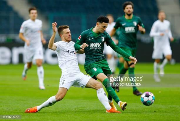 Moenchengladbach's German forward Patrick Herrmann and Augsburg's Swiss midfielder Ruben Vargas vie for the ball during the German first division...