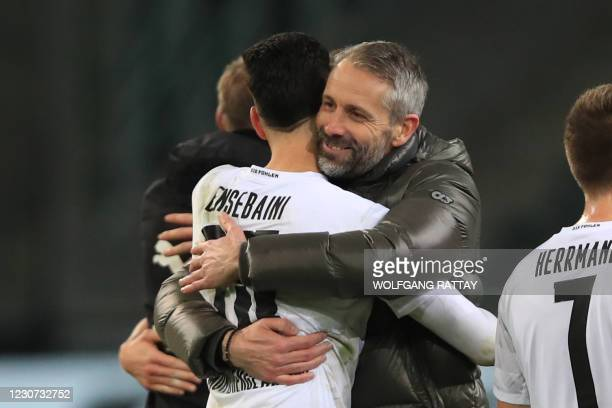 Moenchengladbach's German head coach Marco Rose embraces Moenchengladbach's Algerian defender Ramy Bensebaini after the German first division...