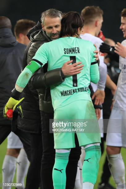 Moenchengladbach's German head coach Marco Rose embraces Moenchengladbach's Swiss goalkeeper Yann Sommer after the German first division Bundesliga...