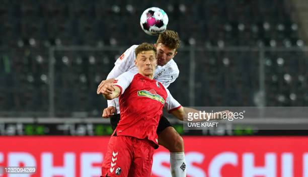 Moenchengladbach's German midfielder Christoph Kramer and Freiburg's German defender Keven Schlotterbeck both jump to head the ball during the German...