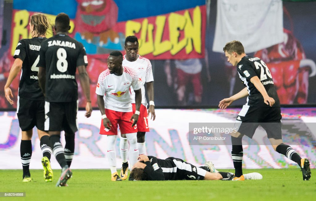 Moenchengladbach´s German midfielder Christoph Kramer lays on the pitch after a heavy foul by Leipzig´s Guinean midfielder Naby Deco Keita (3rd from L) during the German first division Bundesliga football match between RB Leipzig and Borussia Moenchengladbach in Leipzig, eastern Germany on September 16, 2017. /
