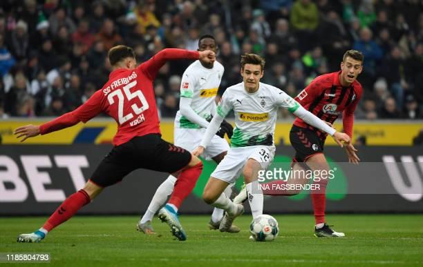 TOPSHOT Moenchengladbach's German midfielder Florian Neuhaus and Freiburg's German defender Robin Koch vie for the ball during the German first...