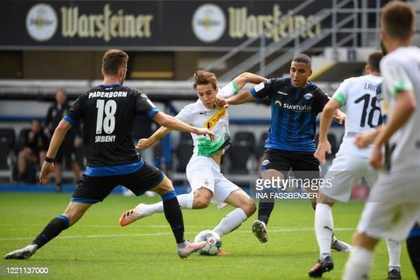 Moenchengladbach's German midfielder Florian Neuhaus and Paderborn's German midfielder Abdelhamid Sabiri vie for the ball during the German first...