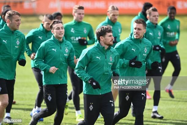 Moenchengladbach's German midfielder Jonas Hofmann and Moenchengladbach's German forward Patrick Herrmann and other players warm up during a training...