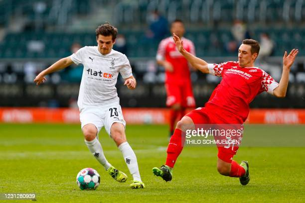 Moenchengladbach's German midfielder Jonas Hofmann and Mainz' German midfielder Dominik Kohr fight for the ball during the German first division...