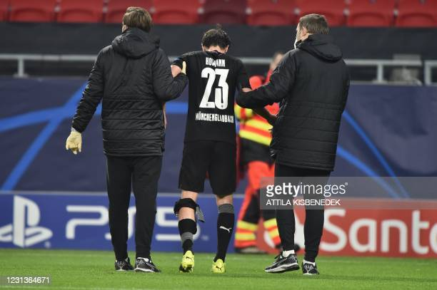 Moenchengladbach's German midfielder Jonas Hofmann is helped off the pitch during the UEFA Champions League, last 16, 1st-leg football match Borussia...