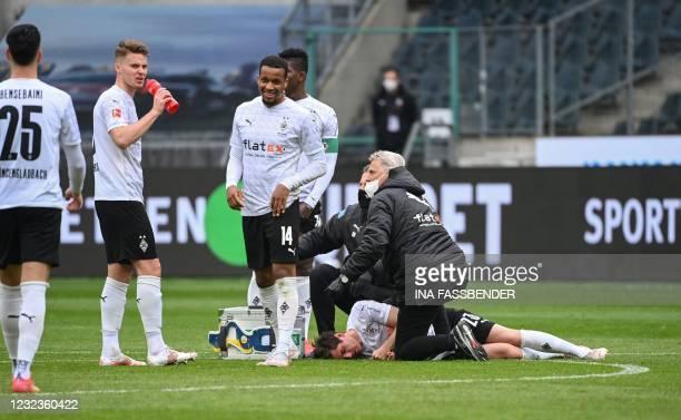 Moenchengladbach's German midfielder Jonas Hofmann lies injured on the pitch during the German first division Bundesliga football match between...