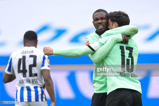 Moenchengladbach's German midfielder Lars Stindl celebrates with Moenchengladbach's French forward Marcus Thuram after he scored a goal during the...