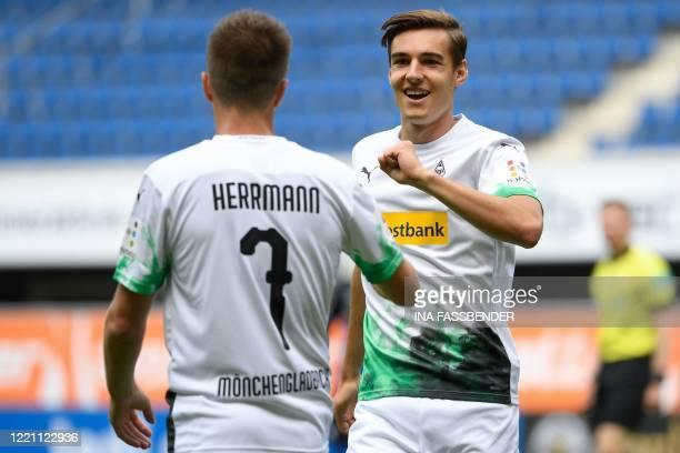 Moenchengladbach's German midfielder Patrick Herrmann celebrates scoring the opening goal with his teammate Moenchengladbach's German midfielder...