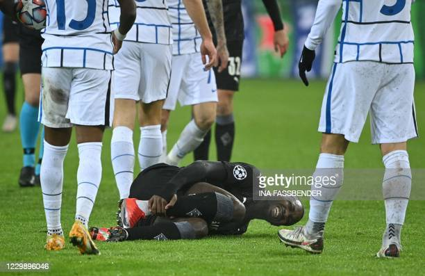 Moenchengladbach's Guinean forward Ibrahima Traore holds his shin after a foul during the UEFA Champions League football match Borussia...