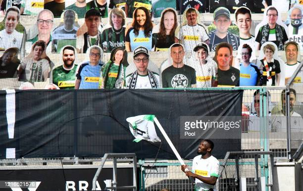 Moenchengladbach's Marcus Thuram celebrates in front of the cardboard cut outs with photos of Moenchengladbach fans displayed on the stands during...