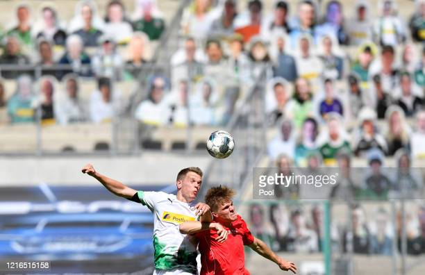 Moenchengladbach's Matthias Ginter, left, battles for possession in the air with Union's Marius Buelter during the Bundesliga match between Borussia...
