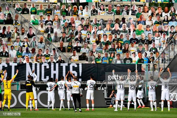 TOPSHOT Moenchengladbach's players celebrate in front of the cardboards with photos of Moenchengladbach fans displayed on the stands after the German...