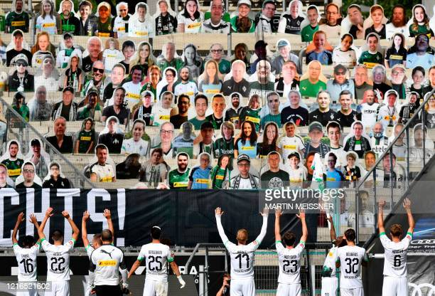 Moenchengladbach's players celebrate in front of the cardboards with photos of Moenchengladbach fans displayed on the stands, after the German first...