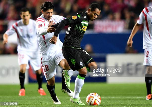 Moenchengladbach's Raffael and Sevilla's Ever Banega vie for the ball during the Europa League Round of 32 soccer match between Sevilla FC and...