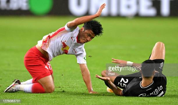 Moenchengladbach's Ramy Bensebaini and Leipzig's Hee-chan Hwang reacts during the Bundesliga match between Borussia Moenchengladbach and RB Leipzig...
